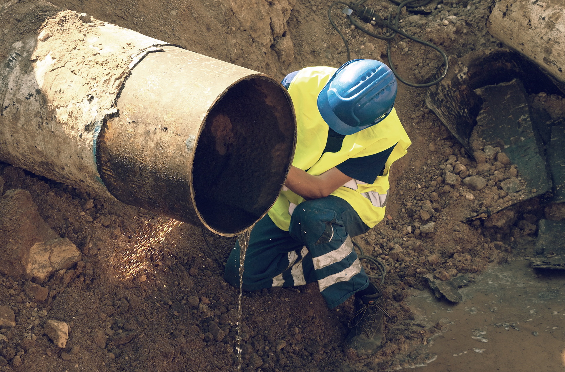 Worker staff is cutting big metal tube with hand grinder. Burning parks are flying down to wet clay. Staff use safety clothes protective boots. Deep excavation pit.